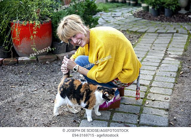 A pretty 42 year old blond woman petting a cat in a garden setting