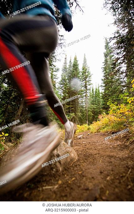 A woman trail running on a cloudy day in Jackson Hole, Wyoming. motion blur