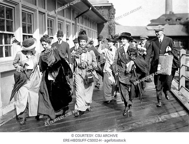 Mrs. Emmeline Pankhurst, the English militant leader center, is shown leaving Ellis Island today with party of suffragists aft