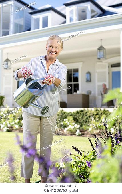 Portrait of smiling senior woman watering flowers in garden