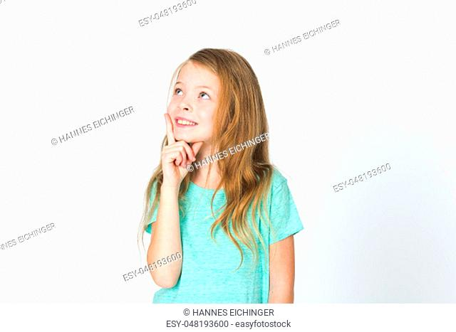 portrait of young pretty blonde girl thinking in front of white background in the studio