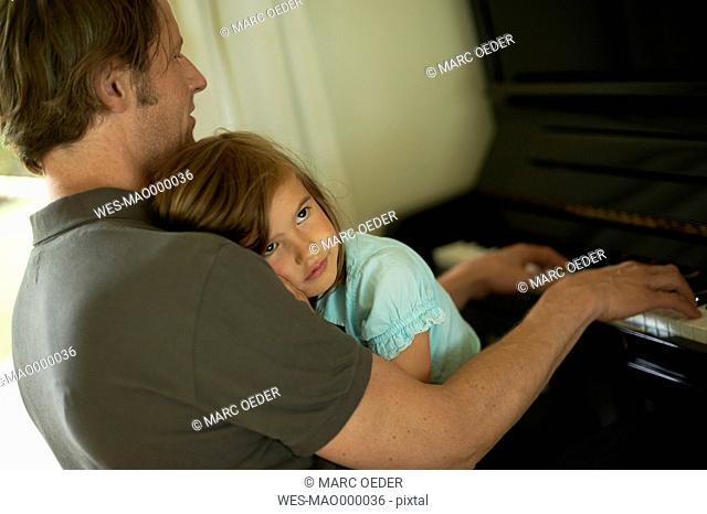 Father playing piano with daughter on his lap
