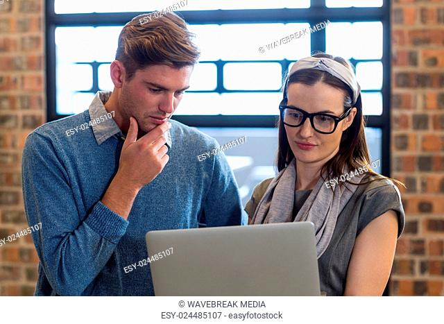 Young colleagues using laptop in office