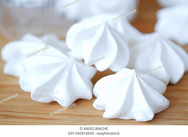 White fresh tasty meringues on wooden table