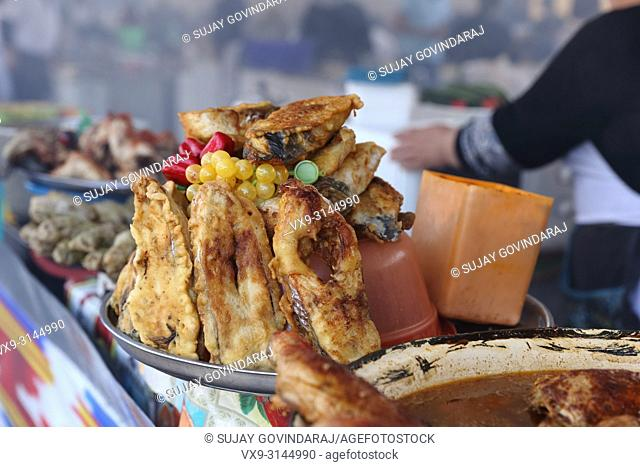 Tashkent, Uzbekistan - May 01, 2017: Spiced up fried fish arranged by a vendor at food court