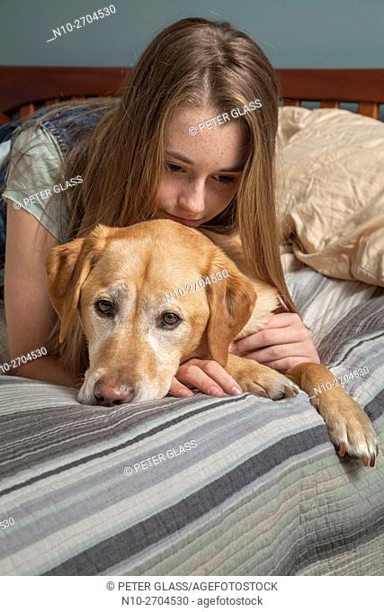 Teenage girl with her pet dog, on her bed