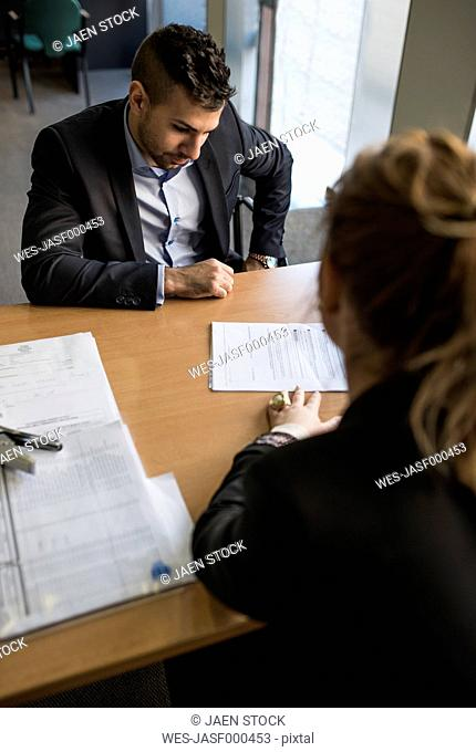 Man and woman in office sitting opposite