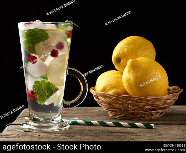 glass with lemonade and pieces of ice, red berries and paper tubes, a refreshing summer drink on a black background