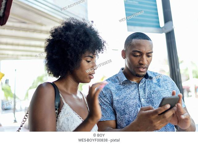 USA, Florida, Miami Beach, young couple using cell phone in the city