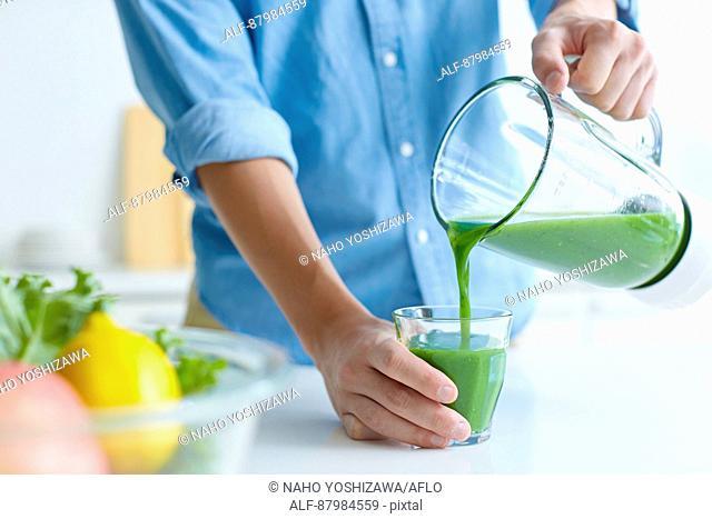 Japanese man making smoothie in the kitchen