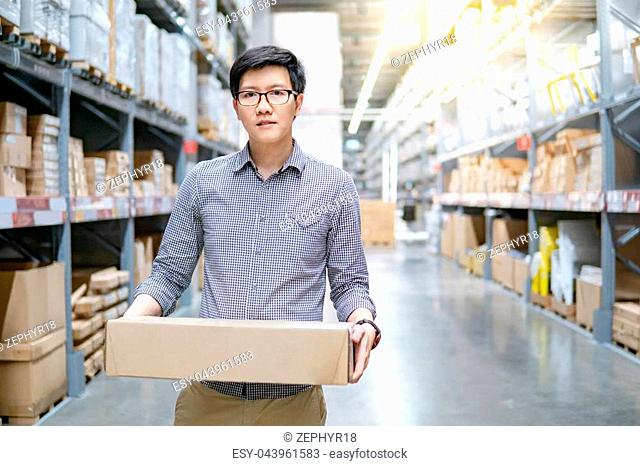 Young Asian man carrying cardboard box between row of shelves in warehouse. Shopping warehousing or working pick and packing concepts