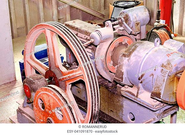 Part of industrial lift. Pulley wheel and engine in engine room. Reconstruction of industrial lift