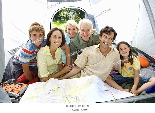 Multi-generational family sitting inside tent on camping trip, looking at map, smiling, portrait