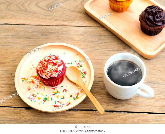 Red cupcakes put on a spherical wooden plate. Beside of cupcake have white coffee mug. In the background have yellow cupcake and chocolate cupcake