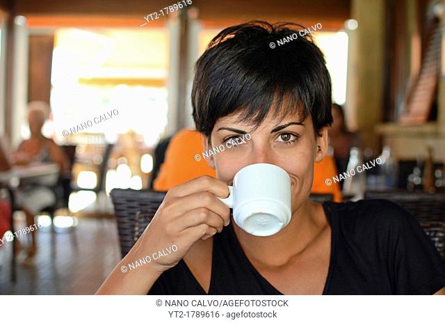 Young woman drinks coffee after lunch