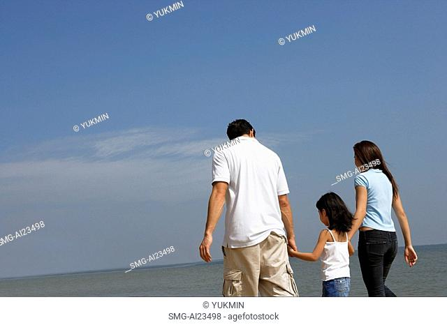 Family holding hands, walking down the beach