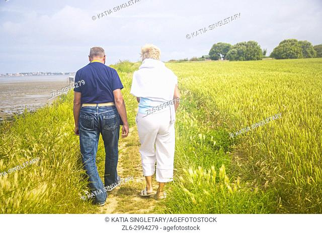 A caucasian couple in their 70's walking side by side in the green wheat fields by the ocean