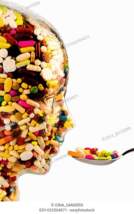 a head made of glass filled with many tablets. symbol photo for drugs abuse and painkillers