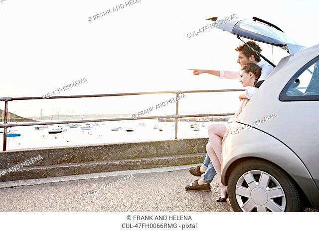 Couple looking out from trunk of car