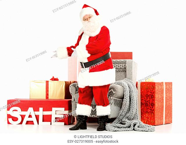 Happy Santa Claus standing near a pile of Christmas gifts with and pointing on Sale sign