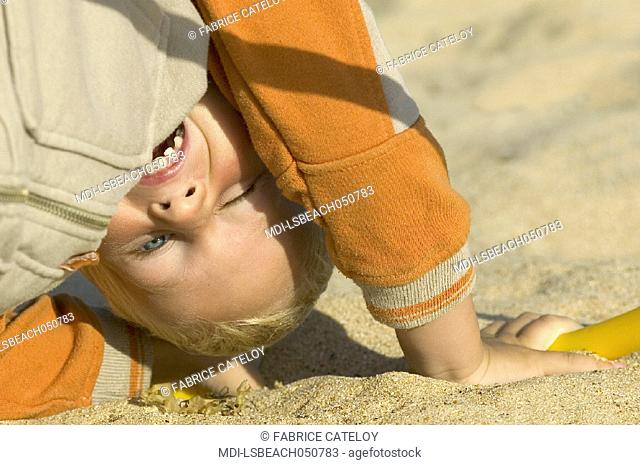 Portrait of a little boy on the wrong side playing on the beach