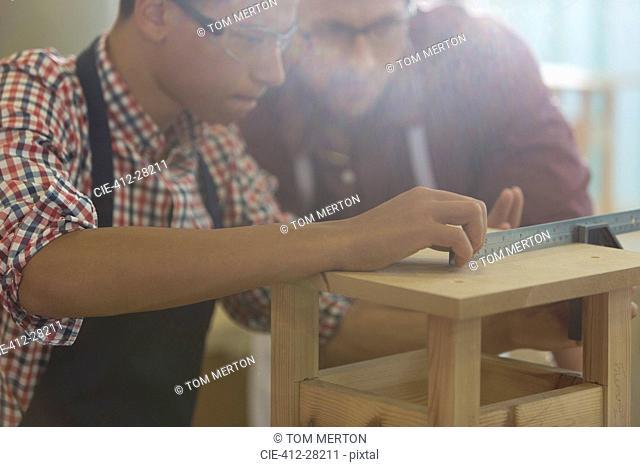 Focused carpenters measuring wood with ruler in workshop