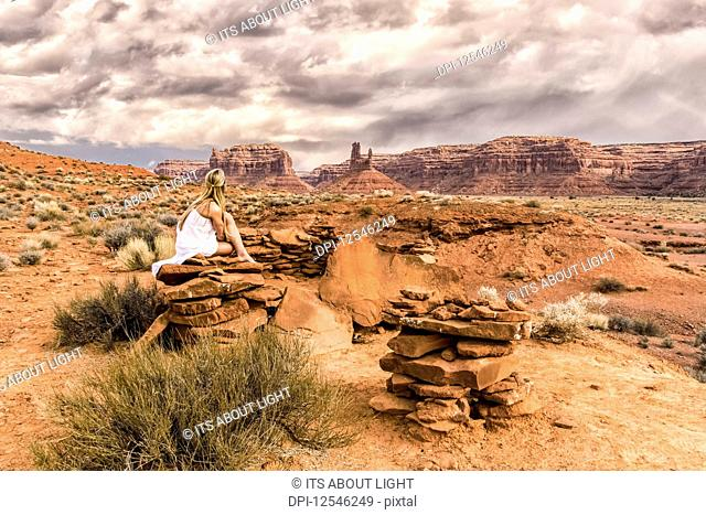 A woman sits on a rock in the Valley of the Gods; Utah, United States of America