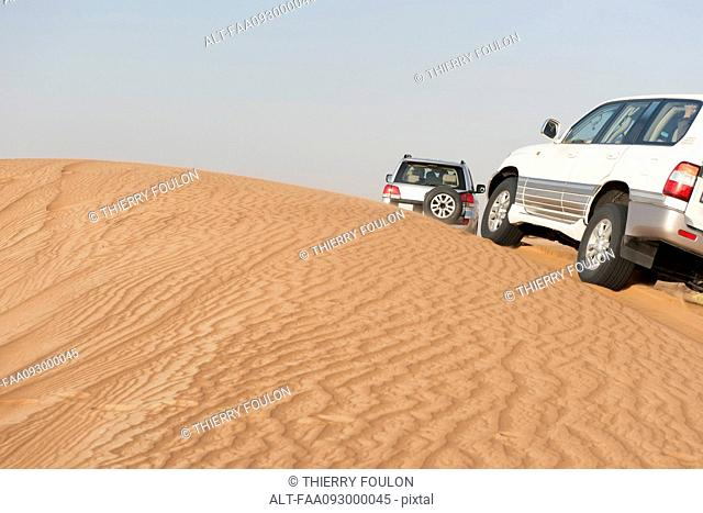 Sports utility vehicles driving up desert sand dune