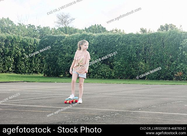Young girl skateboarding alone at a basketball court