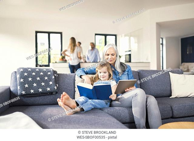 Grandmother and granddaughter sitting on couch, reading together book and tablet pc