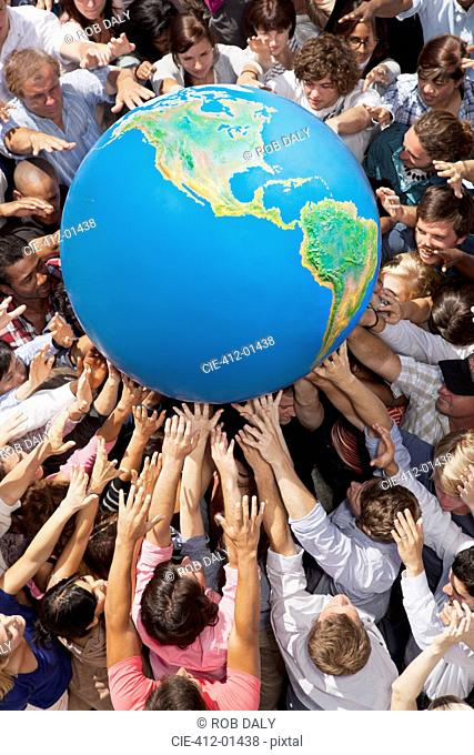 Crowd of people reaching for globe