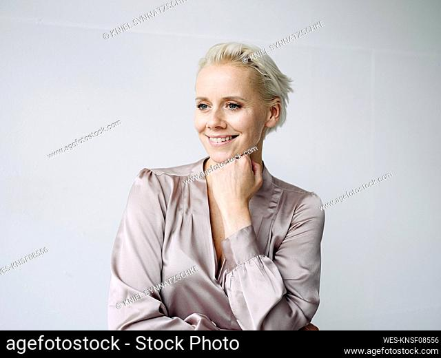 Smiling businesswoman with hand on chin looking away against white wall in office