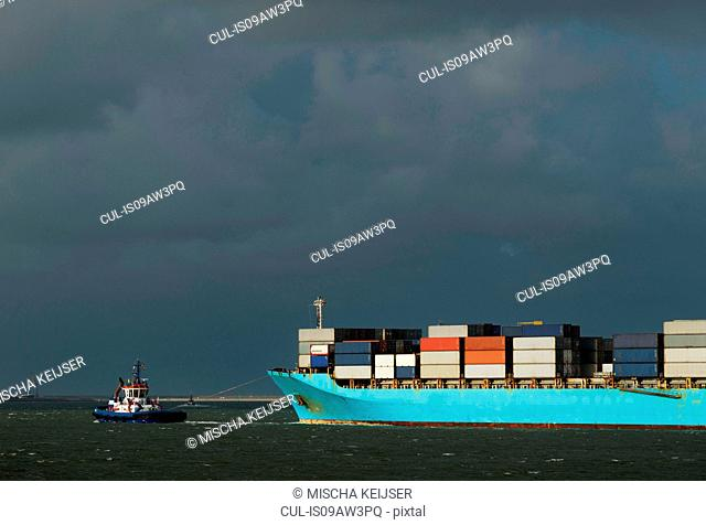 Container ship entering Rotterdam harbour with help of tug boat