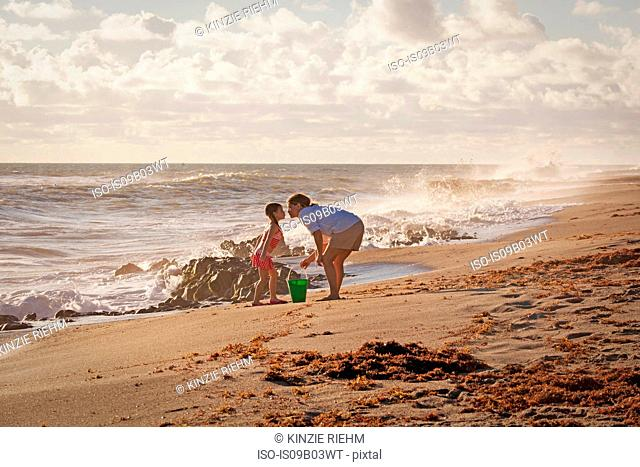 Mature woman and daughter puckering for a kiss on beach, Blowing Rocks Preserve, Jupiter Island, Florida, USA