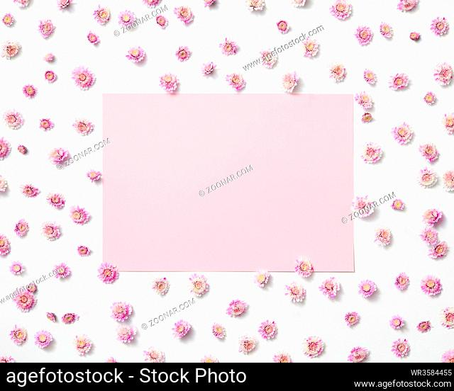 Greeting photo frame from blossoming small flowers and pastel pink rectangular place for text. Flat lay. Valentine's Day concept