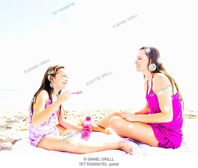 Mom and her daughter (6-7) sitting on blanket on beach