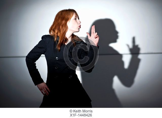 A late teen early 20s single woman girl with red hair pointing her fingers like a gun, casting shadow, blowing her lips, UK