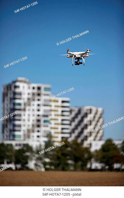 Drohne fliegt in blauem Himmel in der Nähe von Hochhäusern