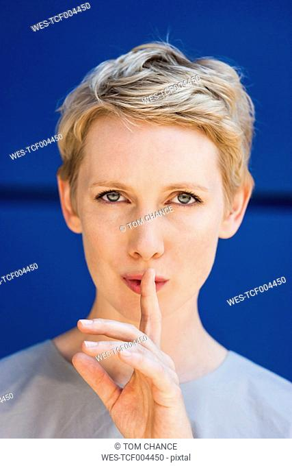 Portrait of blond woman with finger on her mouth in front of blue background