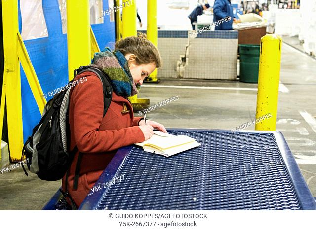New York City, USA. Young, brunette woman writing her notes while sitting at a table inside the New Fulton Fish Market, Hunts Point, The Bronx