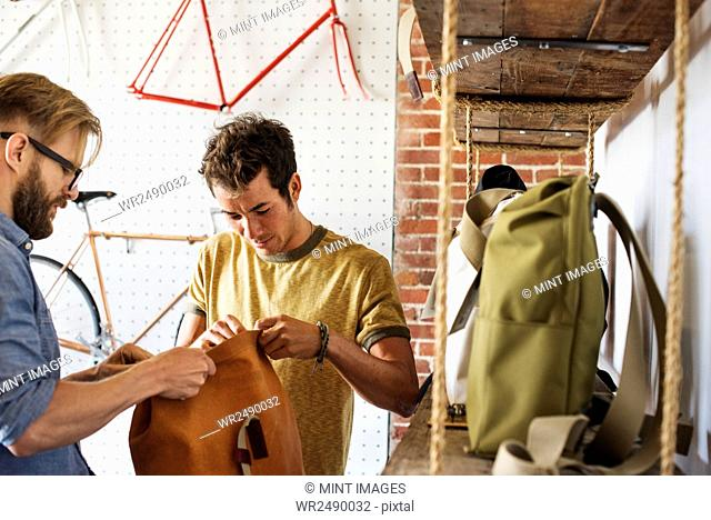 Two men in a cycle repair shop, a client looking at backpacks and bike packs