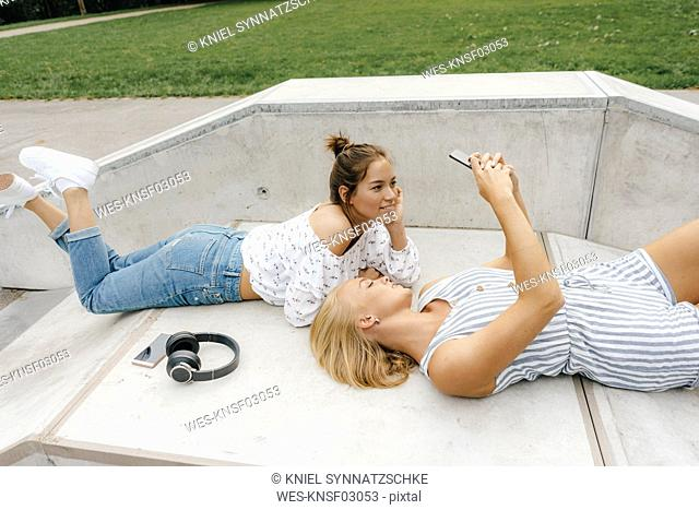 Two happy young women with cell phone and headphones in a skatepark