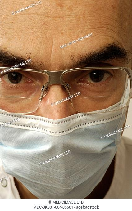 A dental surgeon wearing a surgical mask and protective eye wear