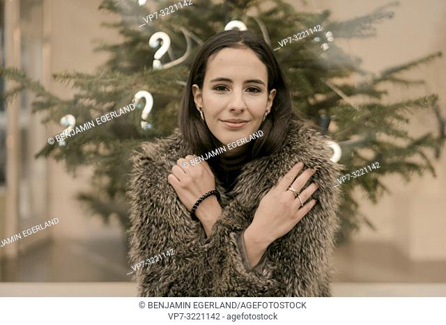 content woman in front Christmas tree with lights of question marks, in Munich, Germany