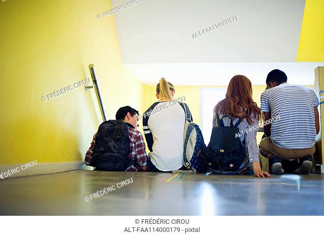 Students sitting together in stairwell, rear view