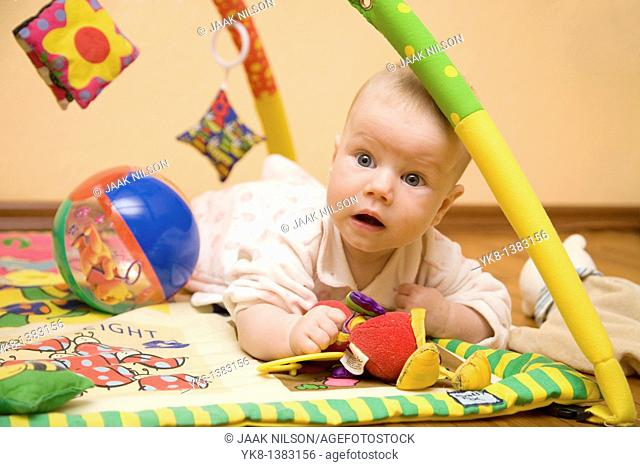 Four month old infant lying on playground with toys