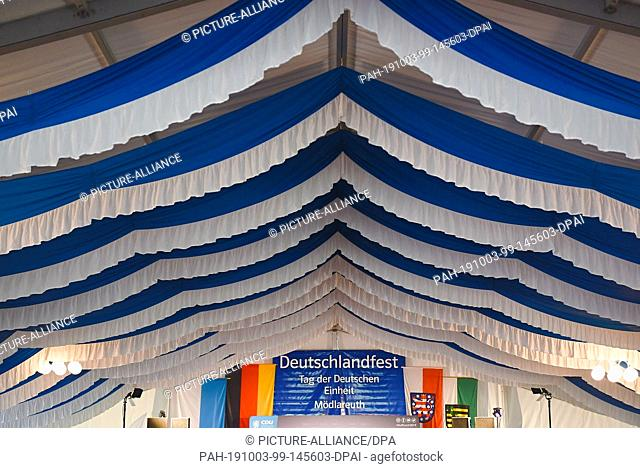 "03 October 2019, Thuringia, Mödlareuth/Töpen: In the marquee of the CDU/CSU a banner with the inscription """"Deutschlandfest - Tag der Deutschen Einheit..."