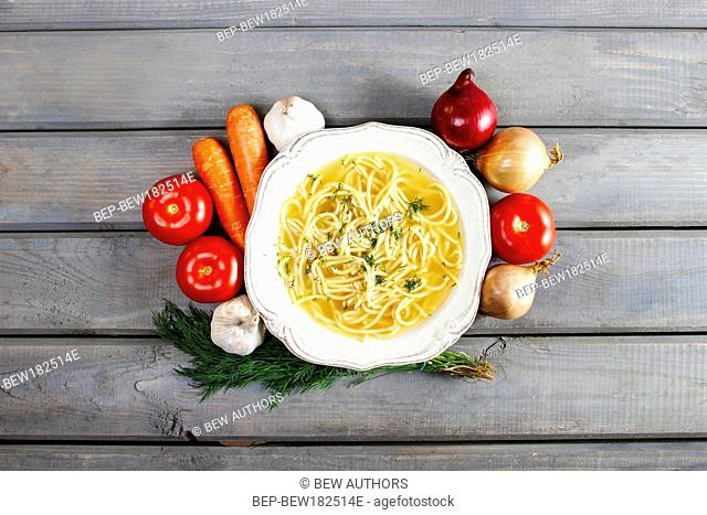 Bowl of chicken soup with noodle. Fresh, raw vegetables around. Top view, copy space