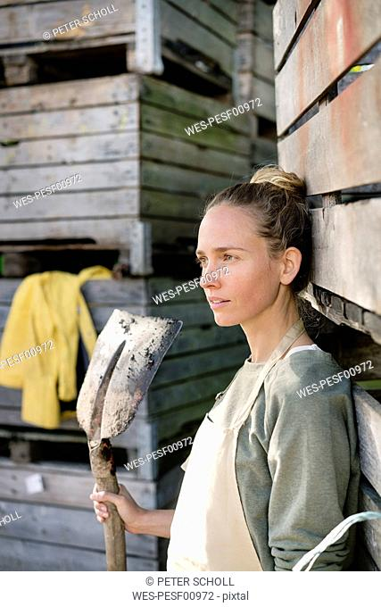 Thoughtful woman leaning against wooden boxes