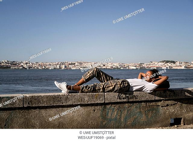 Young woman lying on a wall at the waterfront, Lisbon, Portugal
